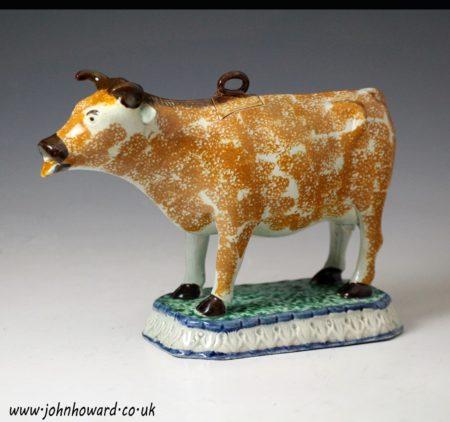Antique English pottery figure of a cow creamer in Prattware circa 1800