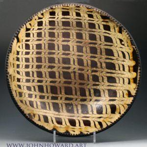 English slipware earthenware circular baking dish profusely  decorated with an elaborate lattice pattern.