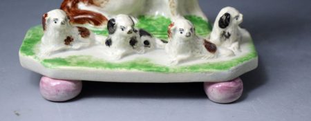Antique English or Scottish pottery figure of a spaniel with four pups on bases with ball feet.