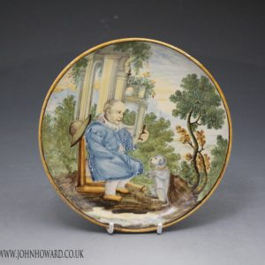 Italian pottery dish with  figure offering a morsel to a dog 17th century