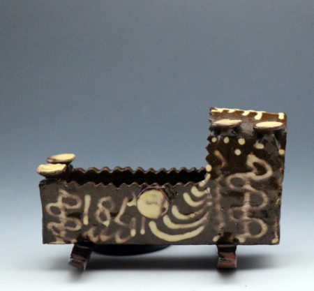 Antique English earthenware cradle dated 1847 and with the initials M:I in slip decoration.